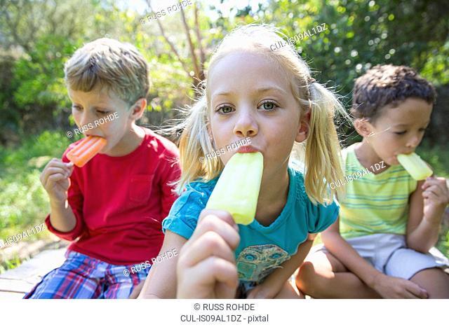 Portrait of three children in garden eating ice lollies
