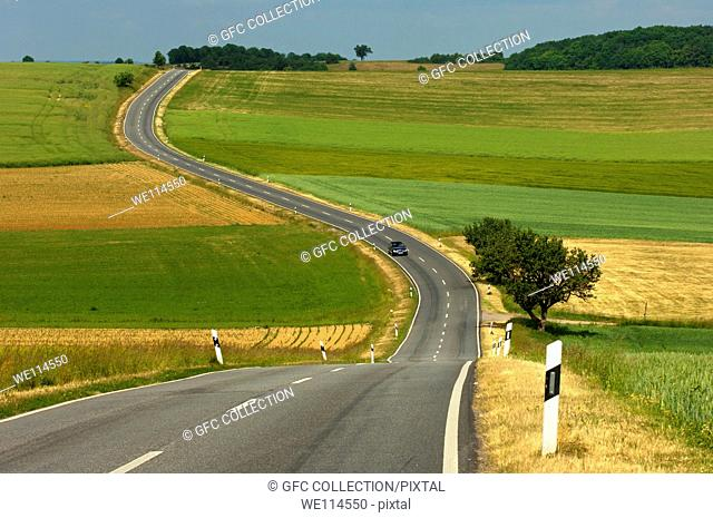 Country road meandering through fields in a rolling landscape, Rhineland-Palatinate, Germany