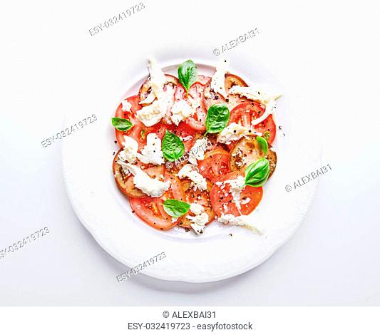 Traditional Italian dish Caprese salad on white plate on white background, fork near it. Basil leaves, mozzarella cheese and juicy tomatoes seasoned with black...