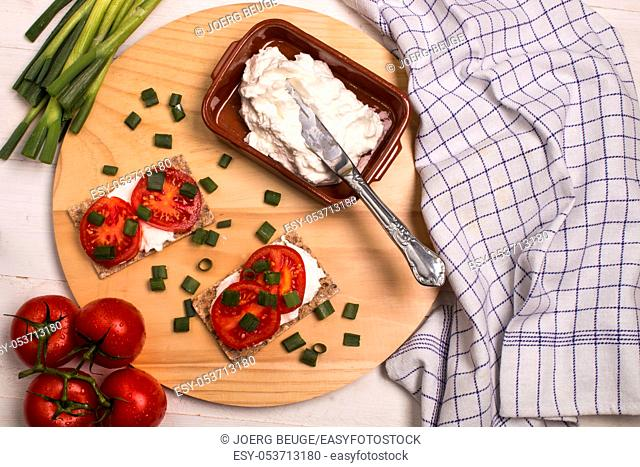 healthy and vegetarian breakfast with crispbread, quark, tomatoes and spring onions on a wooden board