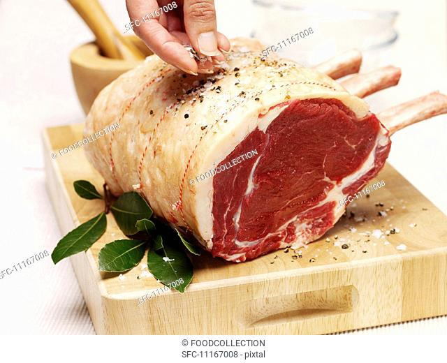A joint of beef being seasoned