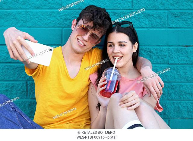 Young couple taking selfie with smartphone in front of blue brick wall