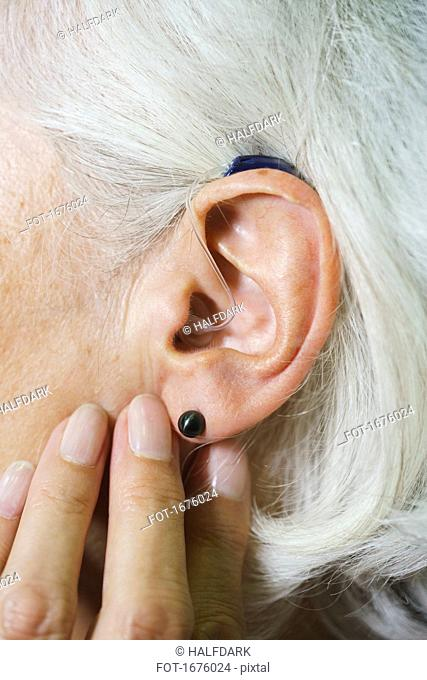 Cropped image of senior woman wearing hearing aid