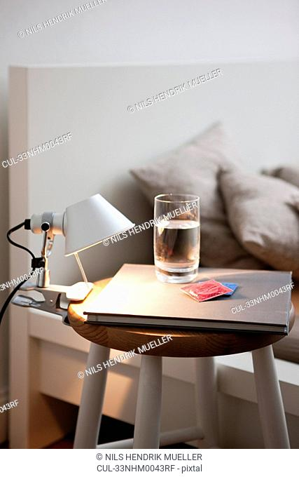 Condoms and water on bedside table