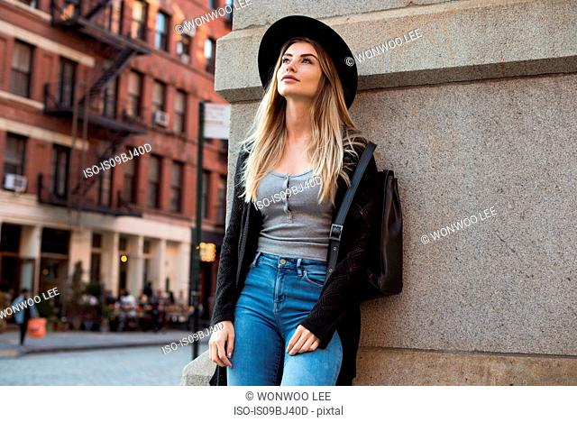 Portrait of woman leaning against wall looking up, New York, USA