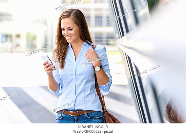 Smiling woman looking at cell phone outdoors