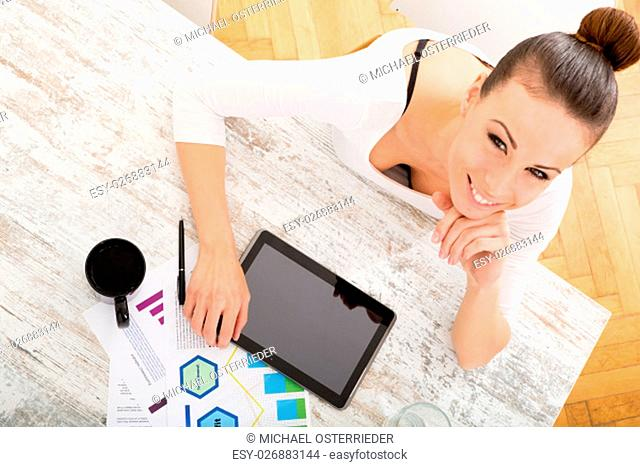 A young adult woman developing a business plan with her tablet PC at home