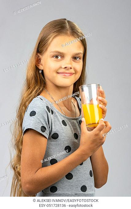 The girl proudly holds a glass of juice