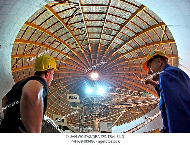Construction workers discuss the remaining work in the new giant circular warehouse of the SKW Stickstoffwerke Piesteritz chemical company in Wittenberg
