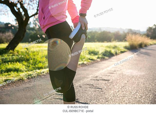 Young woman exercising in rural setting, stretching leg, low section