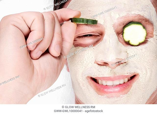Cucumber slices on a man's eyes