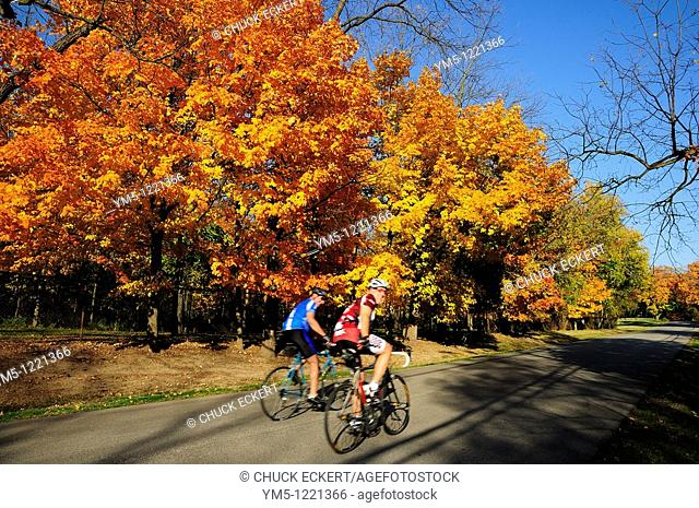 Two blurred bicyclists riding down autumn country road in Northern Illinois