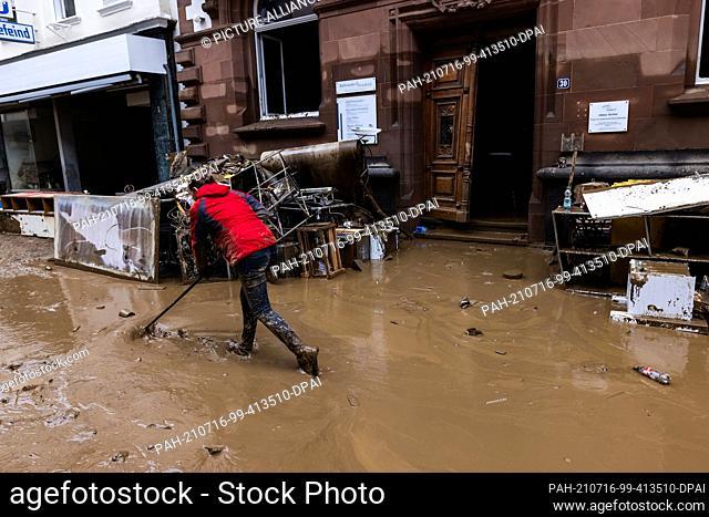 16 July 2021, Rhineland-Palatinate, Bad Neuenahr: A woman pushes mud through the street. Massive rainfall has caused flooding in Bad Neuenahr in...