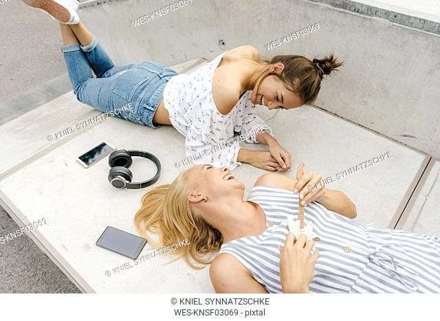 Two happy young women lying on ramp in a skatepark making music