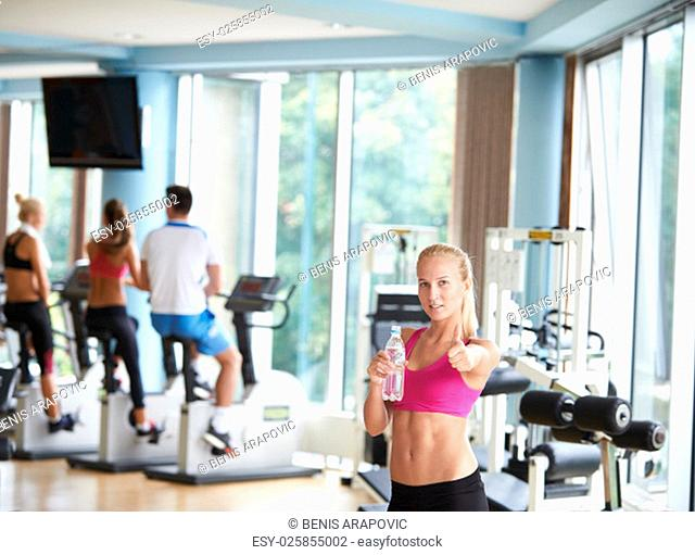 young healthy blonde woman in fitness gym drink water