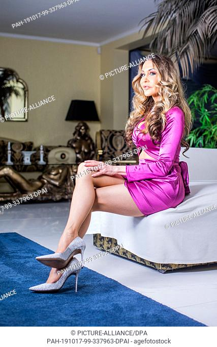 17 October 2019, North Rhine-Westphalia, Wesel: Dolly Buster, painter, author and former erotic actress, sits in the living room of her house