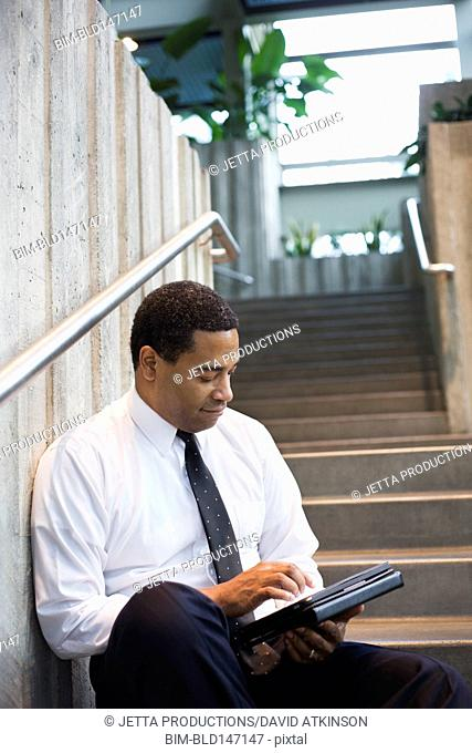 African American businessman using digital tablet on stairs