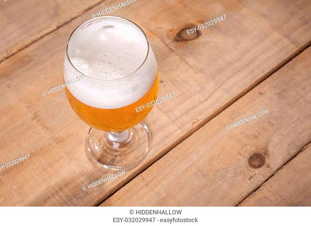 Glass of light beer with tall white foam head on a wooden table