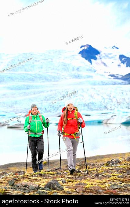 Adventure hikers travel people walking with hiking poles on Iceland by glacier and glacial lagoon / lake of Fjallsarlon, Vatna glacier