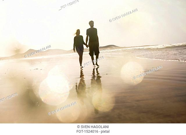 Full length of couple holding hands while walking at beach