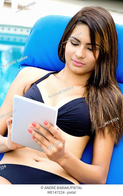 Young attractive woman is using a tablet at vaction while relaxing in a lounge chair at a swimming pool