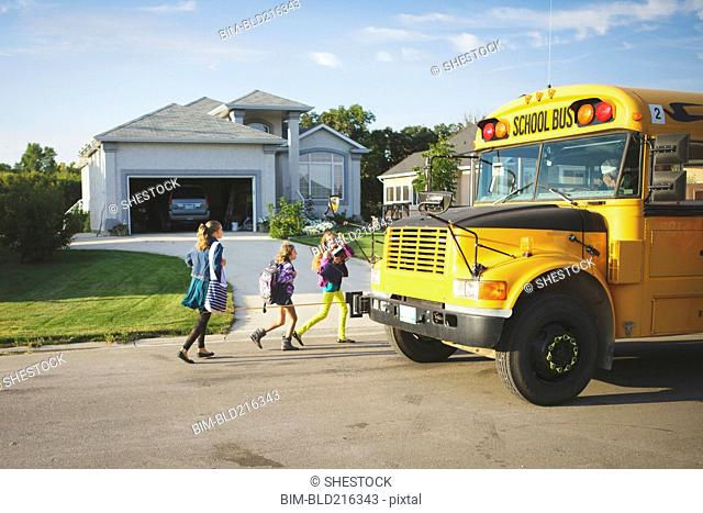 Caucasian girls walking to school bus