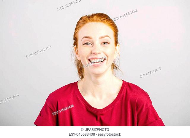 Happy cheerful young woman wearing red shirt, looking at camera with joyful and charming smile