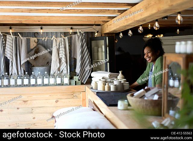Happy female shop owner standing behind counter