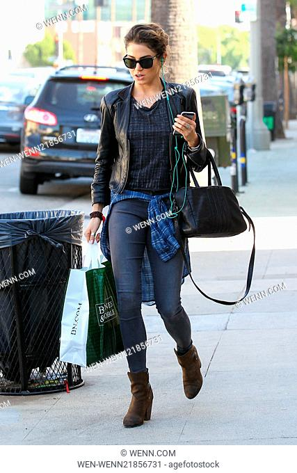 Nikki Reed wearing ear studs complimented by silver rings on her fingers, wearing a light leather jacket, skinny jeans and brown suede boots