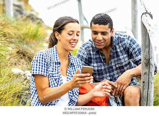 Italy, Massa, smiling young couple using cell phone during a hike in the Alpi Apuane mountains