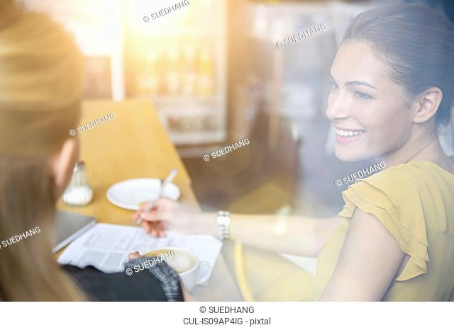 Two female friends having coffee together in cafe