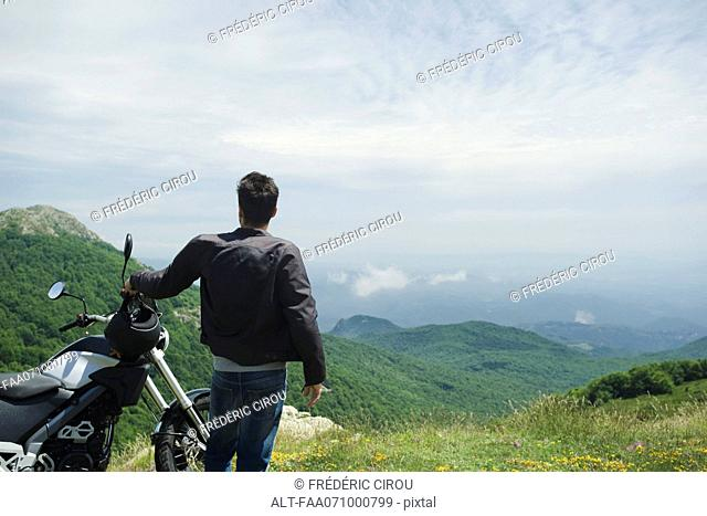 Man standing by motorcycle on mountain, rear view