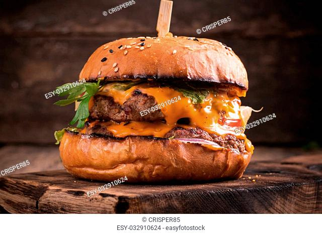 Tasty grilled burger with lettuce and mayonnaise ,on a rustic wooden table of counter, with copyspace
