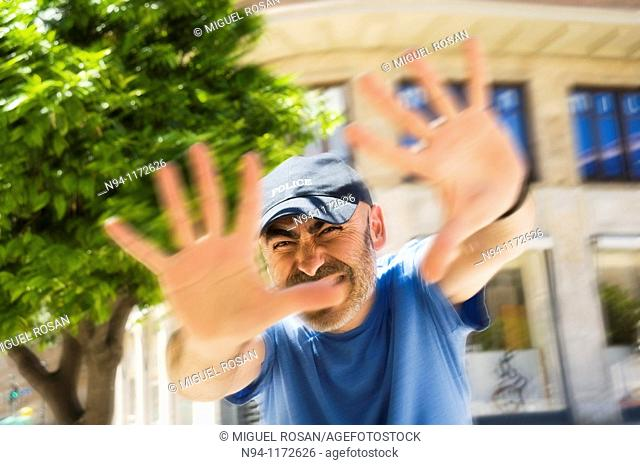 Middle-aged man with a beard and cap, in the center of the city, with open hands scold the photographer