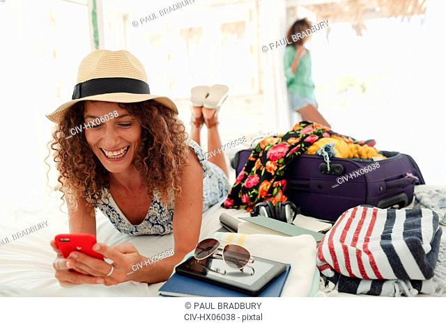 Happy young woman using smart phone, unpacking suitcase on beach hut bed