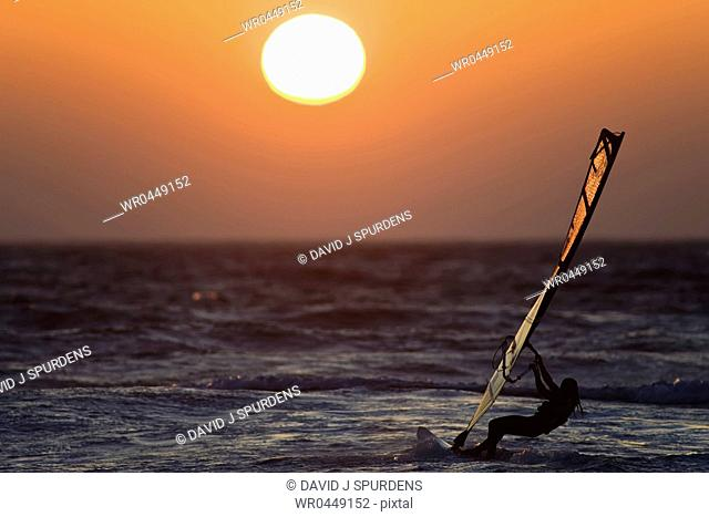 A windsurfer rides the ocean waves into the sunset