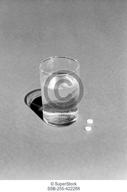 Glass of water and two pills