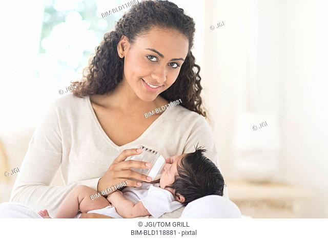 Hispanic mother bottle feeding infant son