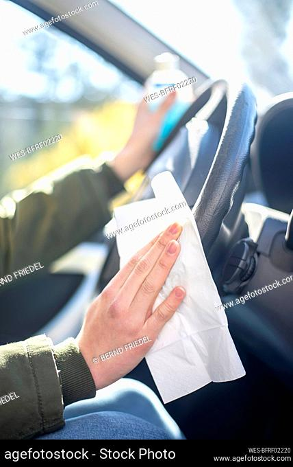 Close-up of woman in car disinfecting steering wheel