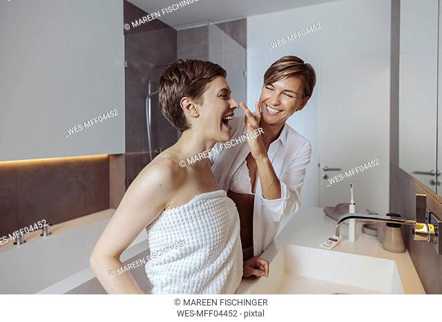 Happy lesbian couple getting ready for their day in the bathroom