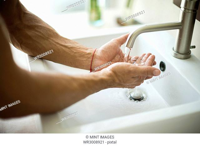A close up of a person washing their hands at a sink