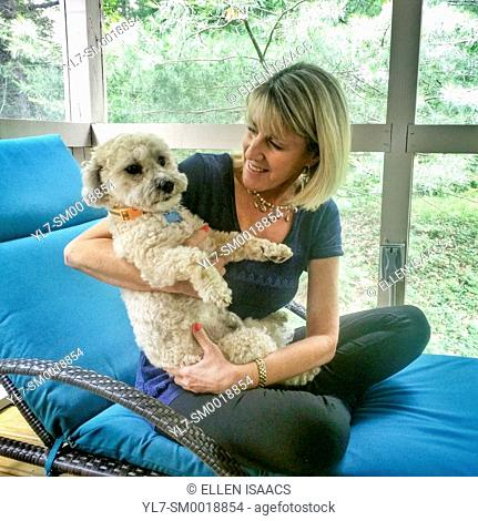 Blonde woman holding a cute white dog on her lap