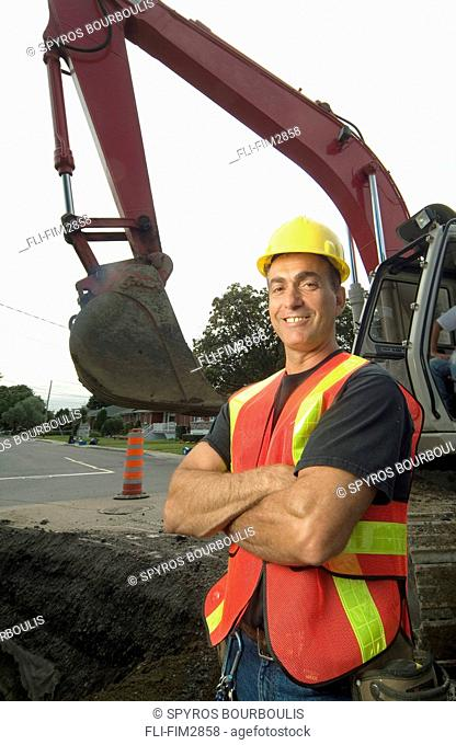 Construction Worker Smiling with Arms Crossed in front of a Front Shovel Excavator, Montreal, Quebec