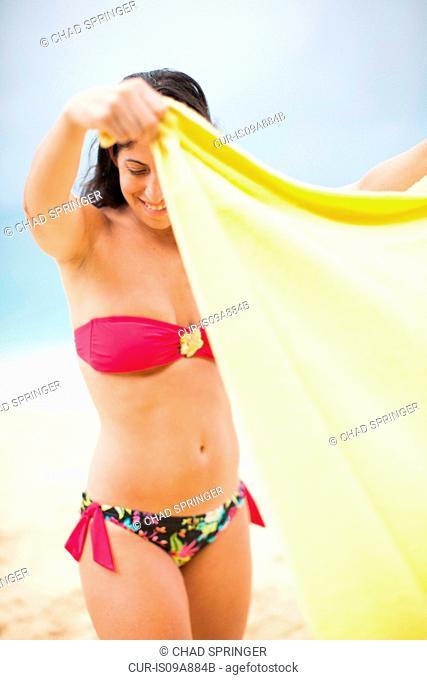 Woman holding yellow towel on beach, St Maarten, Netherlands