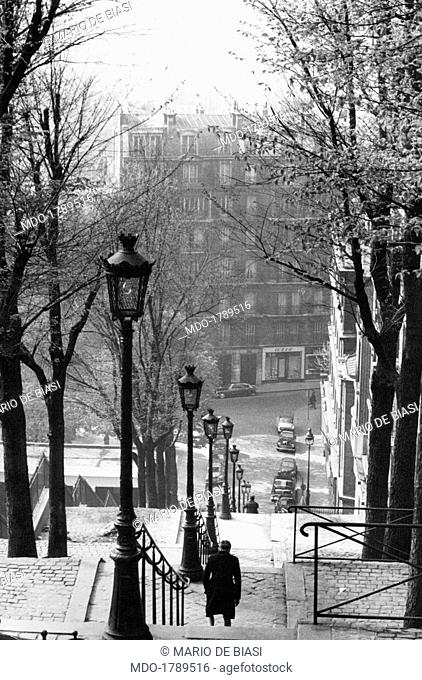 View of the staircase from Montmartre hill, with trees and lantern-shaped lamps running along; on the background can be seen the facade of a palace