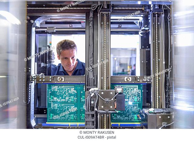 Worker loading circuit boards into testing machine in circuit board factory