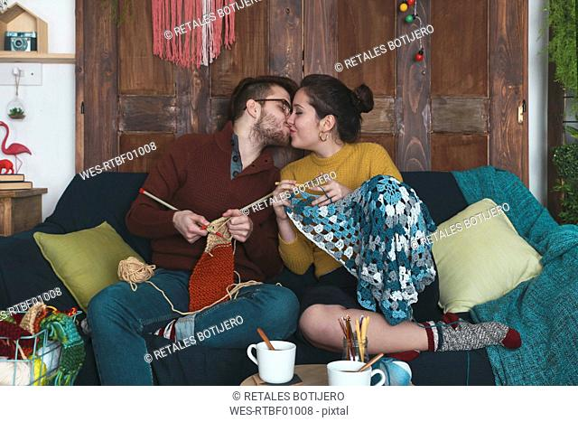 Young couple doing needleworks kissing on the couch