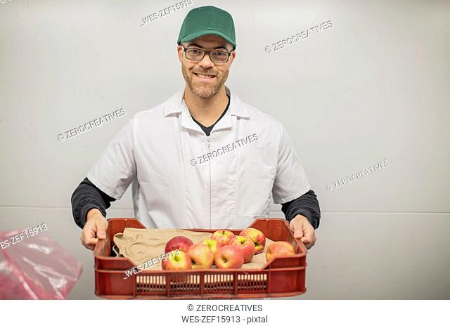 Worker holding apple crate