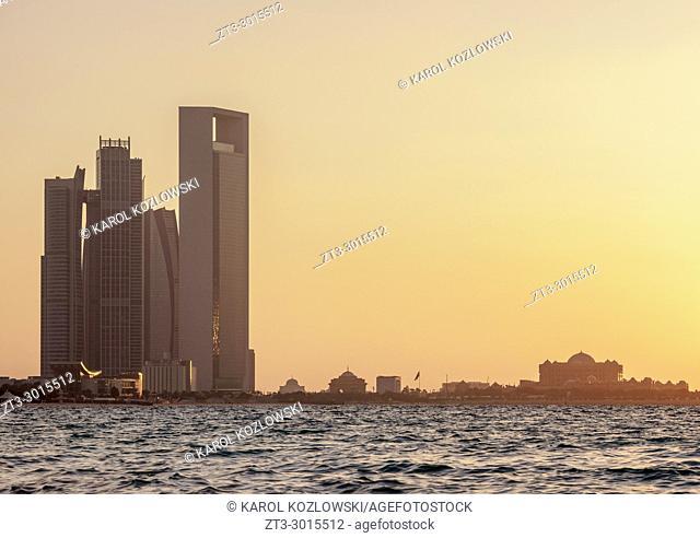 Skyline with Etihad Towers and Emirates Palace Hotel at sunset, Abu Dhabi, United Arab Emirates