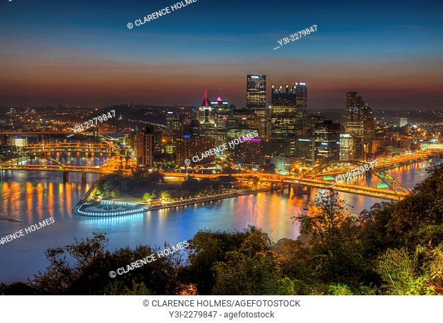 The sky glows orange during morning twilight in the last hour before sunrise over the downtown area of Pittsburgh, Pennsylvania including the skyline, bridges
